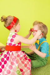 The girl in a bright dress puts on glasses on the boy
