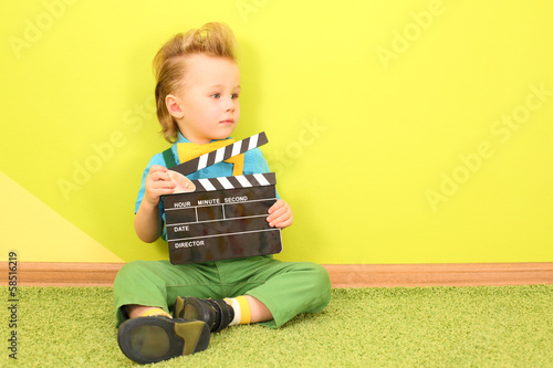 Mod little boy with a clapboard in hands