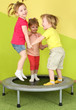 Three smiling children jumping on a trampoline