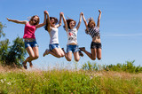 Four happy teen girls friends jumping high at blue sky