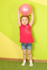 Little girl with pigtails holding a pink ball over her head