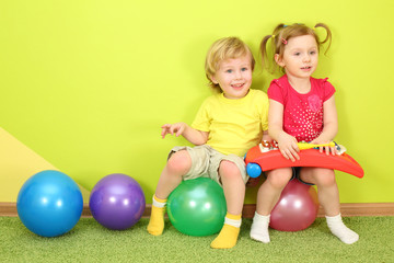 Boy and girl with pigtails sitting on the colorful balls