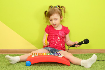 A girl with pigtails playing on metallophone