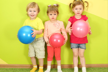 Two girls and a boy standing with balls in hands