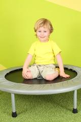 A smiling little boy sitting on a trampoline