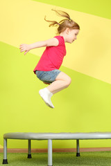 Little girl with pigtails jumping on a trampoline