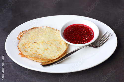 Pancakes with raspberry jam on a plate with a fork