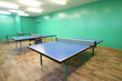 Three blue ping pong tables in the room