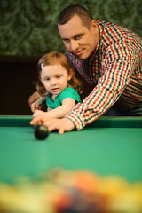 A man teaches his daughter to play billiards