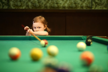Cute little girl with pigtails playing pool