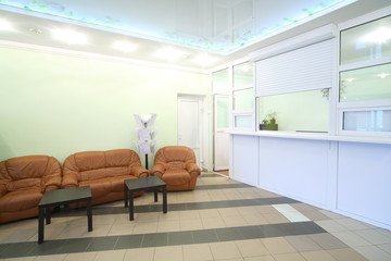 Empty light reception area with two chairs, sofa and tables