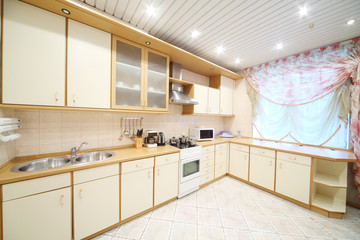 Interior of modern kitchen with beige furniture