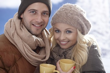 Happy couple drinking tea at wintertime outdoor