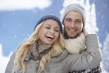 Loving couple having fun in snowfall
