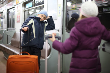 Teen boy and girl in a jacket with suitcases