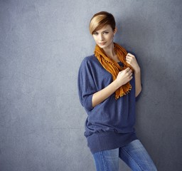 Attractive young woman leaning to wall