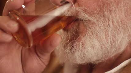 white beard closeup slowly drinking tea of a glass