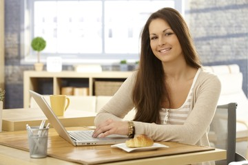 Happy woman with breakfast and laptop
