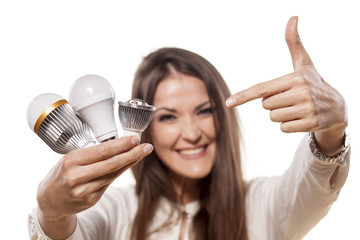 girl holding a LED bulb in one hand and  pointing  at them