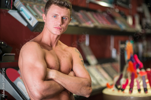 A muscular man with naked torso in store for adults