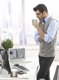 Businessman drinking coffee standing in office