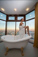 Beautiful half-naked woman  in bathroom with window