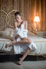 A girl in a white robe sitting on the bed in the bedroom