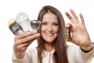 girl holding the LED bulbs in one hand and coins in the other