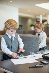 Little boy and girl in business suit playing in business center
