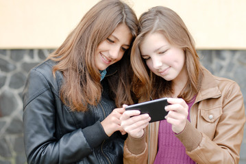 Two happy smiling teen girls looking on smart phone