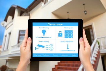 Female hands hold a tablet with system clever house on the backg