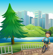 A boy biking across the tall buildings near the river