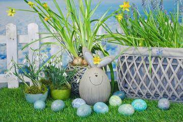 Lustiger Osterhase mit Ostereiern und Blumen auf Wiese