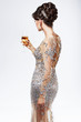 Woman in Silver-Golden Dress with Wineglass of Champagne. Luxury