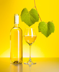 Bottle and glass of white wine with grape leaves