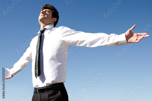 Happy business man raised arms with blue sky