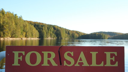 For Sale sign with defocused lake in the background.