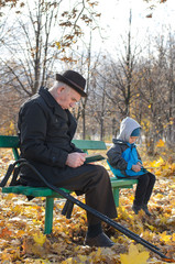 Retired man reading in the park with his grandson