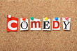 The word Comedy on a cork notice board