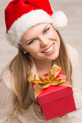 Happy smiling Santa lady wearing warm knitted clothes with gift