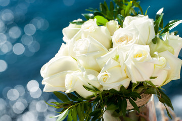 White rose bouquet against blue background.