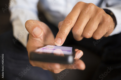 Man using a mobile phone on sofa, indoor