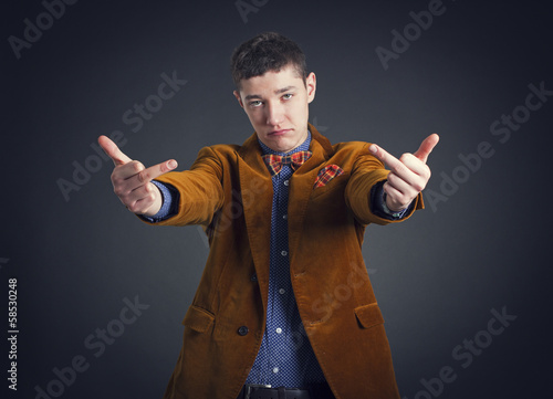 Portrait of a young man with an obscene hand gesture.