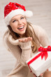 Happy woman with gift box in Santa hat looking at snowflakes