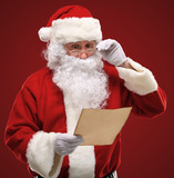 Happy Santa Claus holding Christmas letter and looking at letter