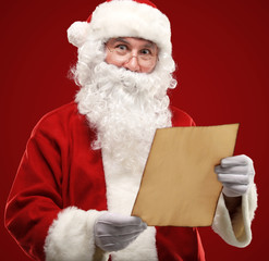 Happy Santa Claus holding Christmas letter and looking at camera