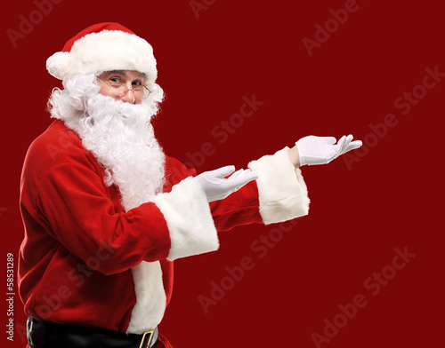 Santa Claus with his arms out in a presenting gesture