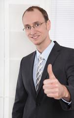 Erfolgreicher lachender Geschäftsmann mit Daumen hoch