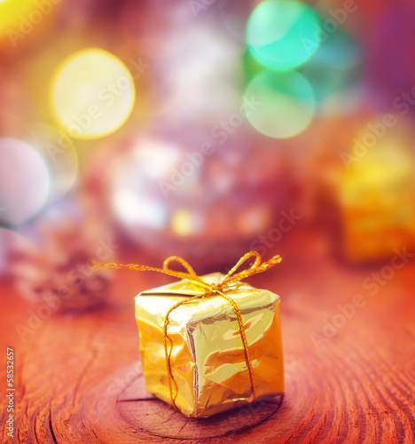 Gold present and cristmas decoration on the wooden board