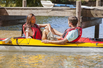 Happy couple in kayaks on lake
